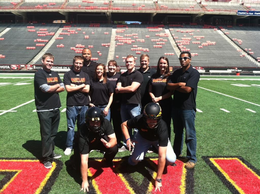 A group photo of the Maryland ticketing group. In the back row, six men and three women are standing. Two men are crouching down in front with helmets on. Everyone is wearing a black Maryland shirt for college colors week.